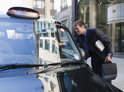 Businessman climbing into taxi cab